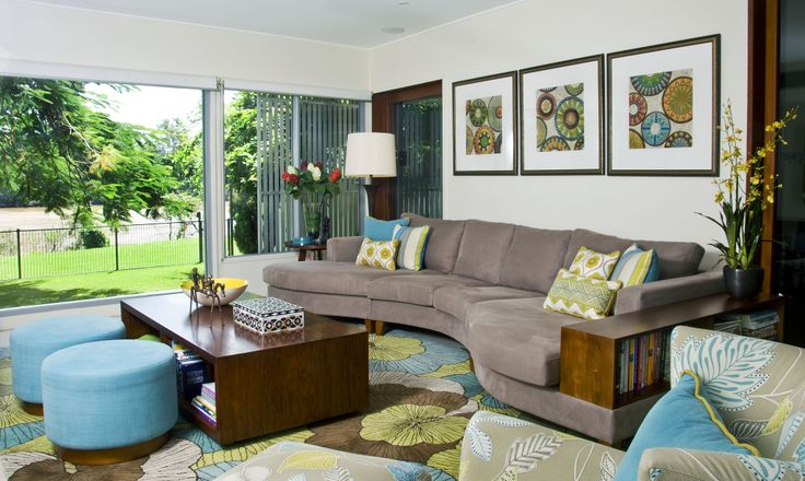 Family room featuring a large modular sofa, rug, armchair, custom ottomans and coordinating artwork and accessories.