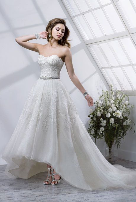 """Brides.com: Wedding Dresses We Love For Under $1,500. Choosing a full-skirted wedding dress with an asymmetrical hem gives you the full princess look while letting you flaunt your modern fashion sense.  Style 4SB810, """"Macie"""" wedding dress, $1,298, Maggie Sottero  See more Maggie Sottero wedding dresses."""