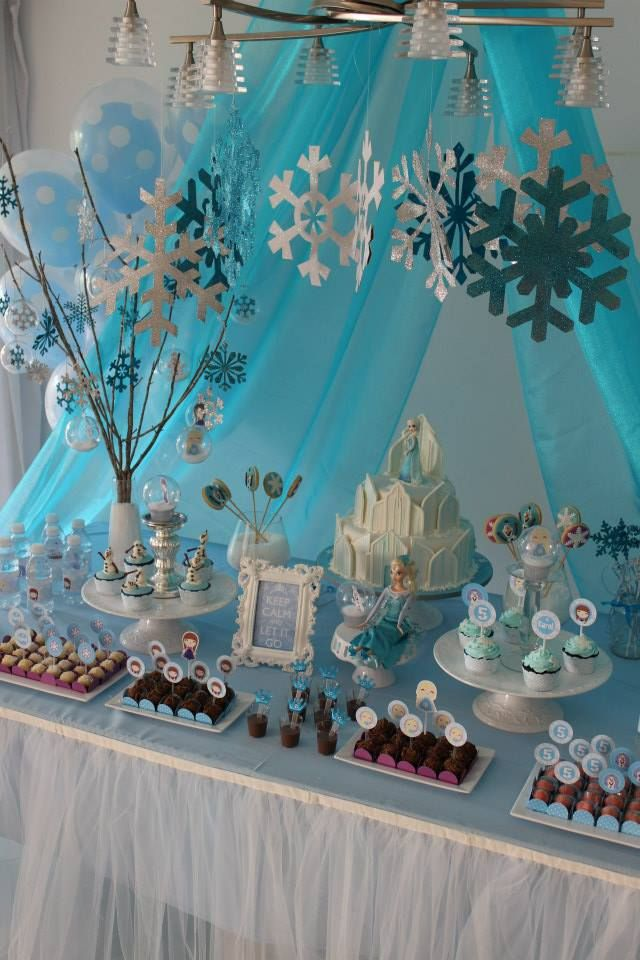 Linda, linda, linda essa mesa! Os blocos de neve pendendo do teto, o bolo no formato do castelo de gelo da Elsa e os docinhos arrumados em blocos com plaquinhas cheias de detalhe. Amamos!