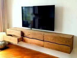 Zwevend tv-meubel van massief eiken planken. Een heel andere uitstraling dan je van ons gewend bent. Wel een strak maar geen rechtlijnig meubel deze keer. Op maat gemaakt met 4 ruime laden en 2 kleppen, behandeld met een donkere olie. De golf volgt zoveel mogelijk de natuurlijke welving van de lijnen in het eikenhout. Elk meubel wordt dan net ietsje anders!Deze is 235 lang en 40 hoog. Hij is 35 cm diep maar 40 kan ook. Andere maten op aanvraag.