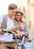 summer holidays, bikes, love, relationship, navigation, gps and dating concept - couple with bicycles and smartphone in the city stock photo...