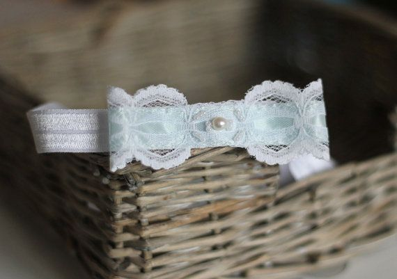 """This bridal garter features a vintage bow, created from a white lace and aqua blue satin ribbon for the traditional something blue"""". It is adorned"""