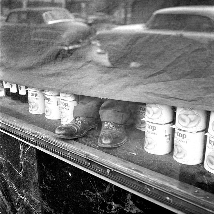 Boy's shoes sticking out from underneath a black curtain in a shop window with cans of peaches on either side. January, 1956, Chicago, IL
