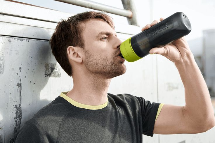 Man on a wall drinking out of a lime fill&go Active