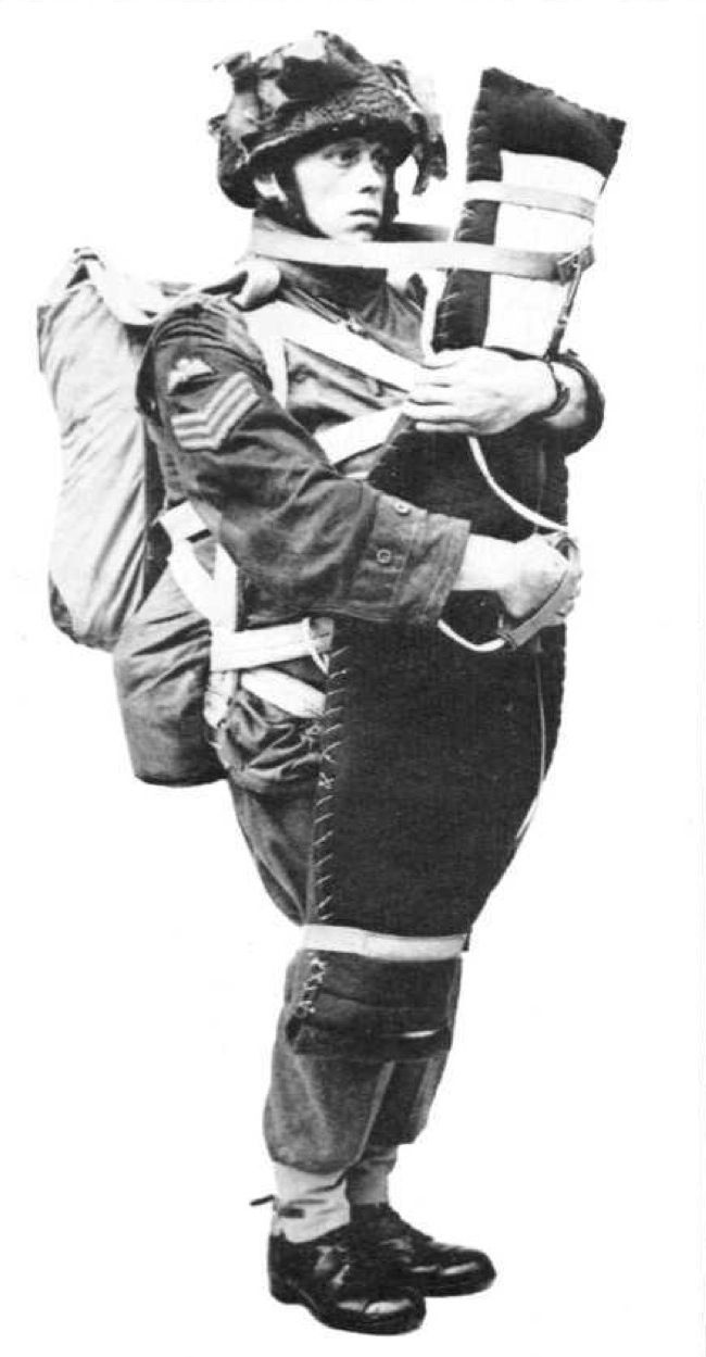 A Sergeant parachutist demonstrating the 'LMG valise' in which the Bren gun was carried on the jump. It was obviously vital for the parachutist to get rid of the heavy valise as soon as his canopy opened since to land with it strapped in this...