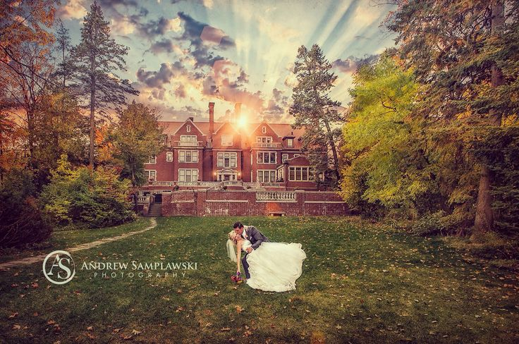 Sunset wedding photo at Glensheen Mansion in Duluth, MN with wedding photographer Andrew Samplawski Photography. Gorgeous wedding gown from Europe. Lovely floral bouquet. Wedding Dip.