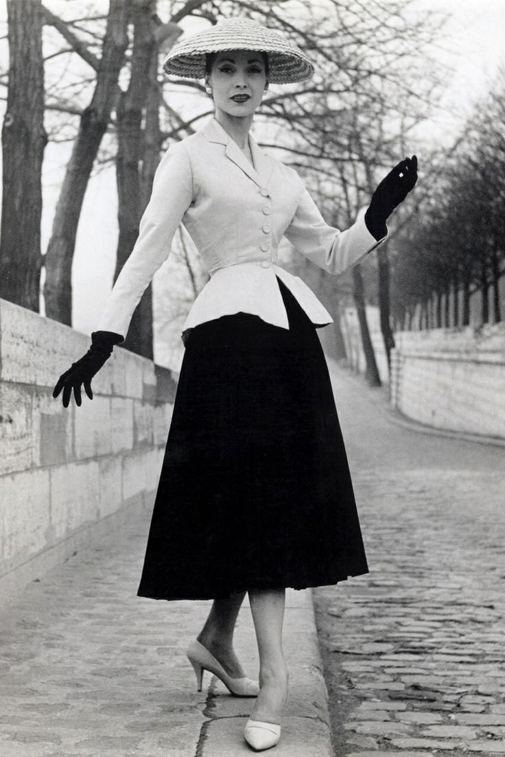 "1940s- Christian Dior's ""New Look"" composed of a suit tailored jacket, padded hips, and a full pleated mid-calf skirt"
