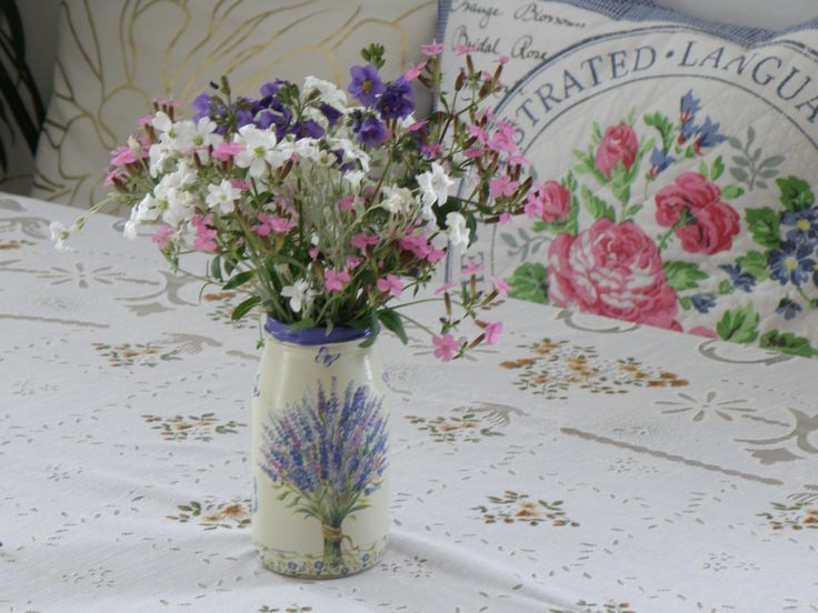Bunch of little spring flowers in home made vase, which is made from jar by decoupage.