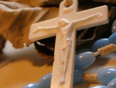 Tento modrý růženec je z plastových korálků. Bílý křížek s reliéfem Krista, je taktéž plastový. Navlačen je na bílé bavlnce, na které jsou znatelné stopy používání.   Délká růžence je 45 cm.