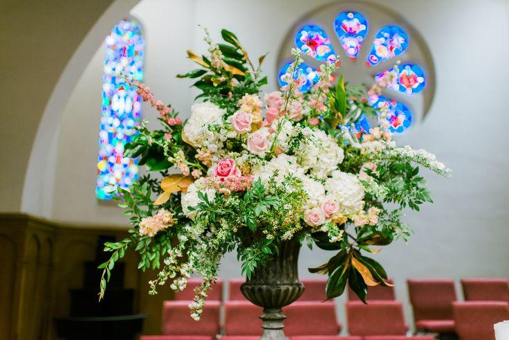 loose altar urn arrangement of white hydrangea, rosita vendela rose, pink larkspur, white spirea, peach stock, magnolia & elm.