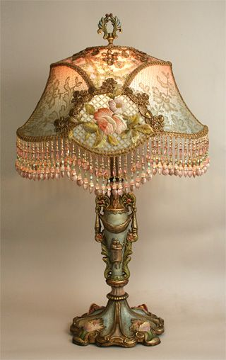 Ornate, Art Nouveau style antique hand painted lamp base holds a French Empire shade. Shade is in colors of pale pink to robins egg blue and covered with metallic laces and wonderful 19th century French embroidered roses and flowers. Hand beaded fringe in matching tones - lights up beautifully.