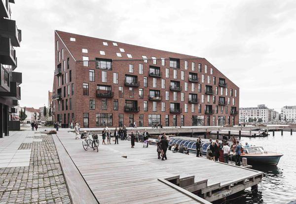 3 architetture monolitiche in mattoni rossi occupano Krøyers Plads nel cuore della città. La sua realizzazione, è legata al processo di partecipazione e coinvolgimento della popolazione residente in tutte le fasi creative, dal concept insediativo, alla scelta dei materiali.