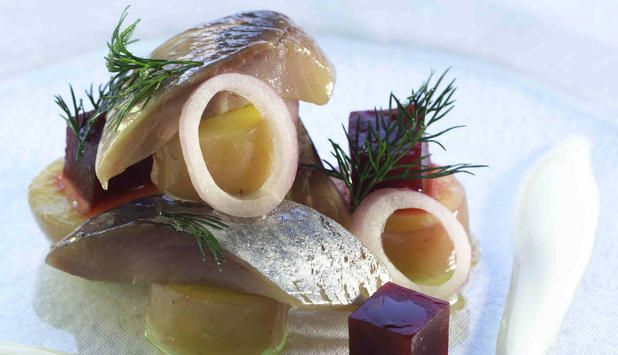 Spekesild med potet, løk og rødbeter servert med rømme og flatbrød er et tradisjonelt måltid. Med frisk dill på toppen er retten komplett.