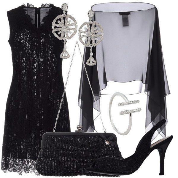 Un abito corto, modello a tubino, in pizzo, coperto dalla cappa in crêpe, nera. Abbiniamo le scarpe in raso, ricoperte di strass, la borsa ricoperta da perline nere, gli orecchini in metallo e strass e l'anello in ottone con zirconi.