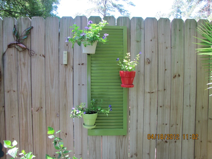 My nieghbor wisley recycled 2 wooden house shutters that some one disgarded. We cut these in half giving us two each.  We painted them and hung potted plants I already had.  This is one of the finished products.   So all it cost me was a can of spray paint.  Neat idea!