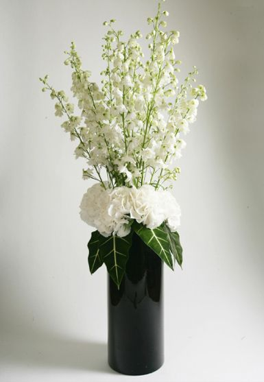 stylish contemporary white floral display in tall black cylinder