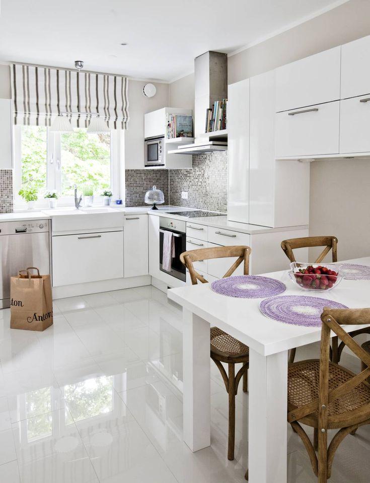 Keittiön välitilassa on sävykäs, ruskea mosaiikkilaatoitus valkoisella saumattuna. Ruskea väri toistuu raidallisessa laskosverhossa, joka teetettiin Isabel B:n kankaasta. Työtaso on kvartsia. Lattia laatoitettiin 30 x 60-senttisillä, korkeakiiltoisilla Laattapisteen laatoilla. Koska kapea tila vaati juuri tietyn kokoisen pöydän, Anna suunnitteli sen itse. Tuolit Rivièra Maison. Pöytätabletit Indiska.