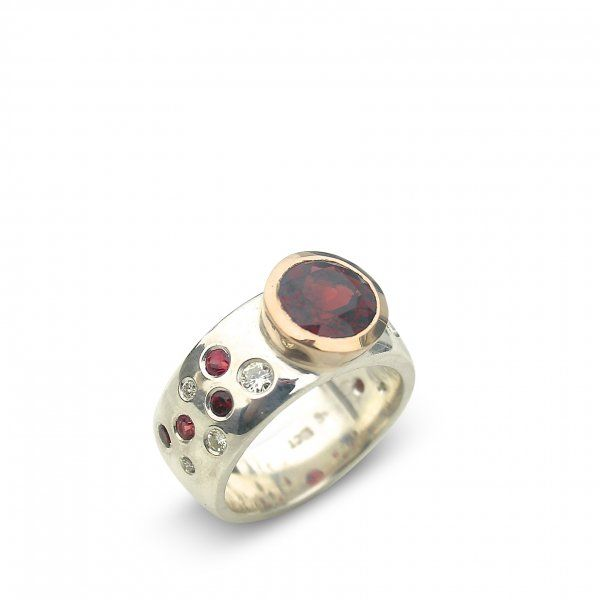 A large juicy deep red garnet of AAA quality (@ 9mm round) set in rose gold on a wide sterling silver band inset with moissanite and red sapphires from $1500.00 custom made in any size