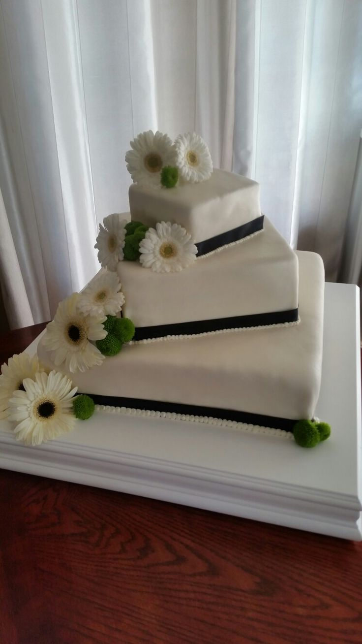 Wedding cake.  With gerbra daisy and a black sash.
