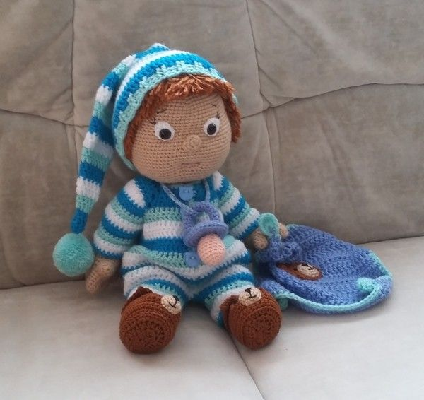Jetzt eine schöne Puppe mit Mütze, eigenem Schmusetuch, Schnuller + hübschen Hausschuhen häkeln. Das macht Spaß + ist auch ein super Geschenk. Leg los.
