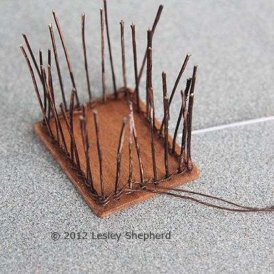 A length of colored thread is looped around the center stake on one end of the dollhouse pastry basket and the thread is 'paired' or twinned around both sides of each stake to weave the basket sides.