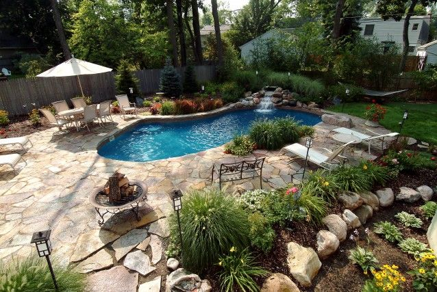 This small backyard was turned into a beautiful and relaxing space. A custom waterfall empties into the pool, which is surrounded by a flagstone patio. Lush landscaping and an assortment of boulders scattered throughout created a very natural look, and a jump rock and putting green were just a few of the details that completed this unique project.