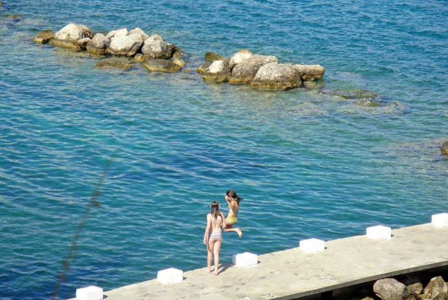 Little girls jumping into the water in Nafplio Yacht Club, Greece