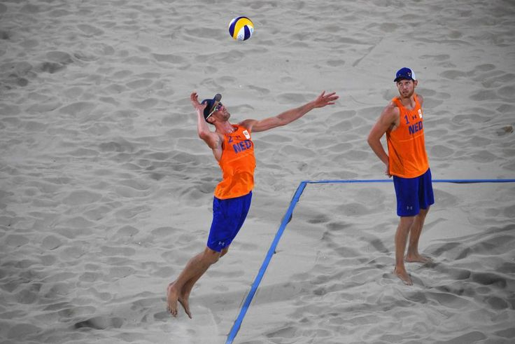 Robert Meeuwsen of the Netherlands serves as Alexander Brouwer looks on during the Men's Beach Volleyball preliminary round…