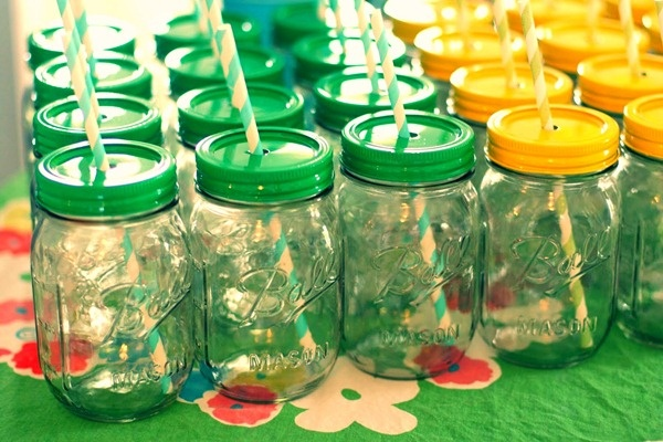 spray painted lids to mason jars with a hole poked in the top for a straw. I like this.