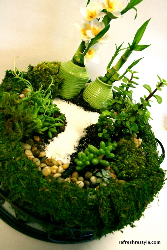 Succulent mini garden with lucky bamboo~planted in an aluminum roasting pan, then placed in a moss lined metal & glass container.  She then used moss to cover all the pan, so it looks like a mini garden in a bowl of moss.  Very creative!