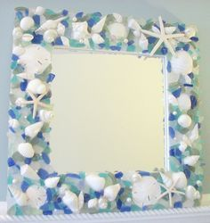 "The Seaglass and Starfish Mirror combines white seashells, a variety of blue and green hand-selected pieces of sea glass, sand dollars, pearls, and white starfish and is shown in ""Bright Mixed""."