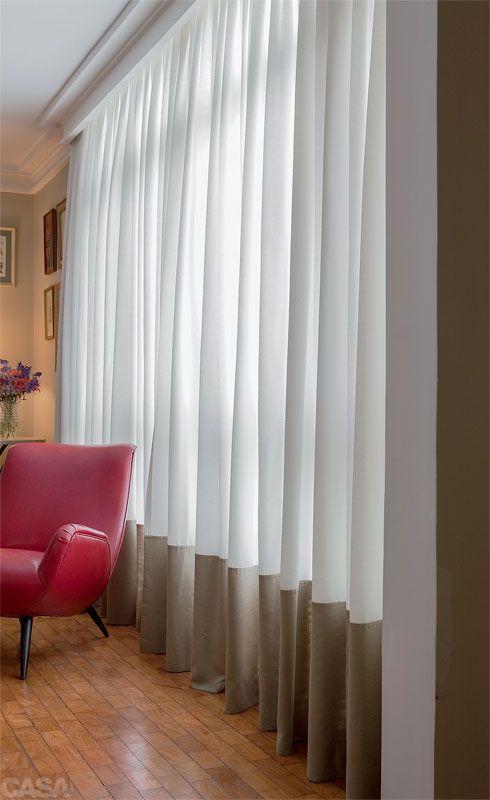 """A elegância da barra alta - Uma proposta pouco convencional foi adotada pelo designer Paulo Rossi, da Interiores Confecções, para fechar o vão de 4 m de largura por 2,70 m de altura da janela de sua sala: barra dupla de 60 cm de altura e de cor diferente do restante da cortina. """"Repeti ali o tom da parede, que é neutro e não interfere na decoração"""", afirma. No barrado, ele usou linho sintético, enquanto o resto da peça é de xantungue misto de seda e poliéster. """"São duas texturas diferentes."""