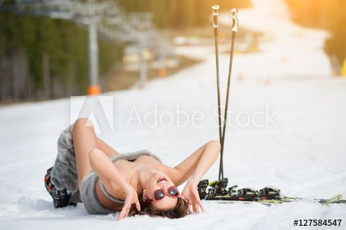 Sexy smiling female skier is lying on snowy slope under ski lift at ski resort. Happy girl is wearing sunglasses, boots. The end of winter season
