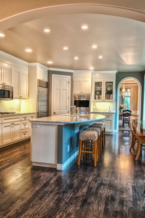 Bright white pairs with dark gray to create a clean, crisp color palette in this open concept kitchen. Recessed lighting brightens the space, and gorgeous wood floors add a touch of rusticity to the design.
