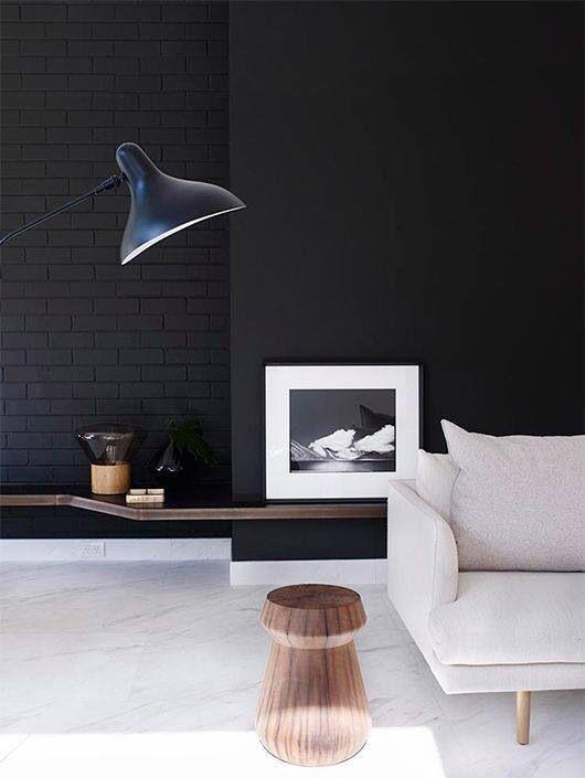 black brick + black wall + stone floor + neutral sofa