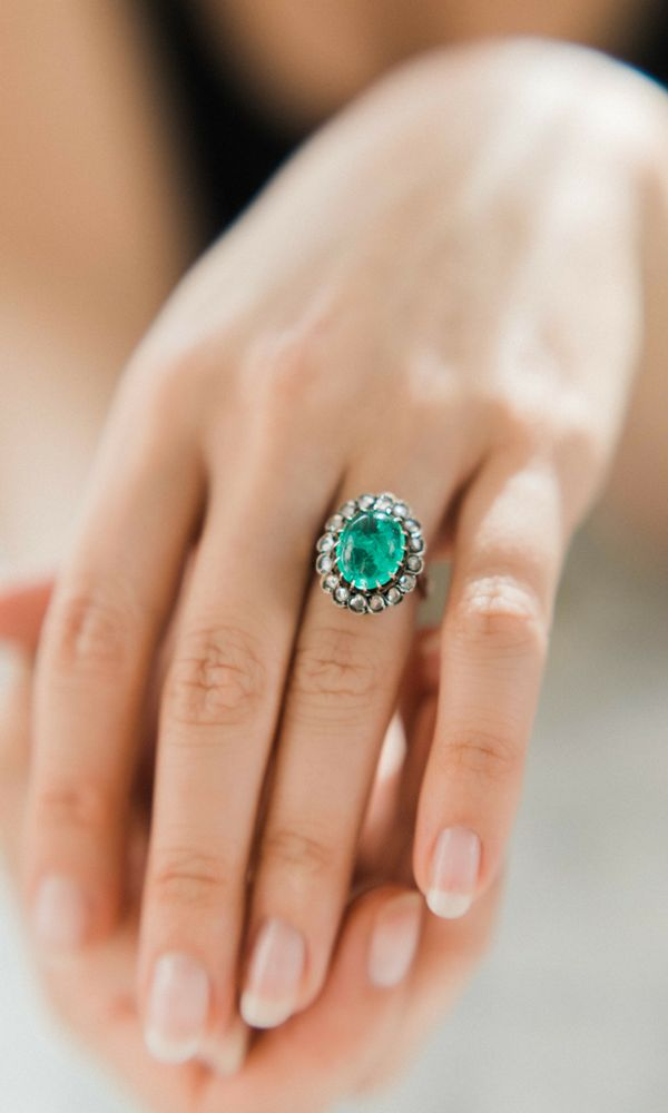 An amazing antique ring with a nearly 6 carat cabochon cut emerald and a halo of rose cut diamonds! The ultimate cocktail ring!