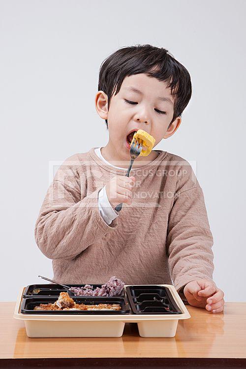 어린이 142, PHO407, 프리진, 사진, 어린이, 사람, PHO407c, 한국인, 동양인, 아시아, 어린아이, 남자, 남자어린이, 소년, 상반신, 1인, 앞모습, 앉아있는, 책상, 학교, 유치원, 음식, 도시락, 급식, 들고있는, 포크, 점심시간, 바라보는, 먹고있는, 입벌린, pho407 #유토이미지
