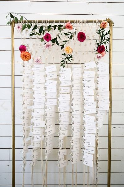 Boho wedding escort card idea - macramé escort card display with bright flowers and white escort cards {Hyde Park Photography}