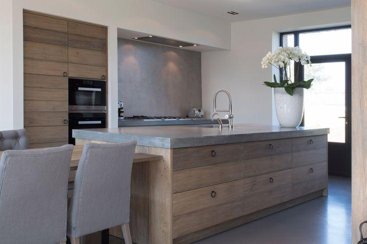 Cucina minimal molto elegante con piano e pavimento in cemento e mobili in legno massello