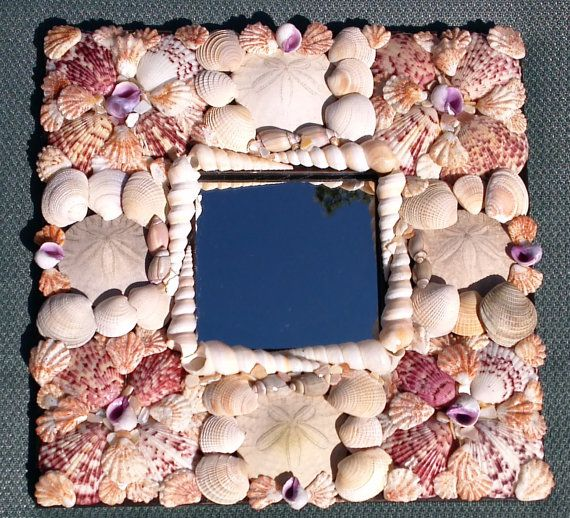This sea shell frame would be a lovely beach décor addition to your home. This is a sea shell frame with a small mirror in the center. There