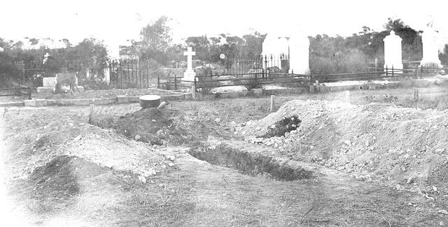 Partial view of a cemetery showing freshly dug graves in the foreground; location unknown, c. 1918