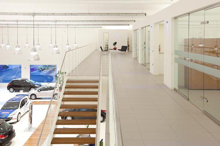 Caporali Contract ha realizzato uno spazio neutro e luminoso per la concessionaria Ugolinelli Peugeot: uno showroom dominato dal bianco per esaltare le automobili esposte e da percorsi in parquet per guidare i clienti all'interno di questo.