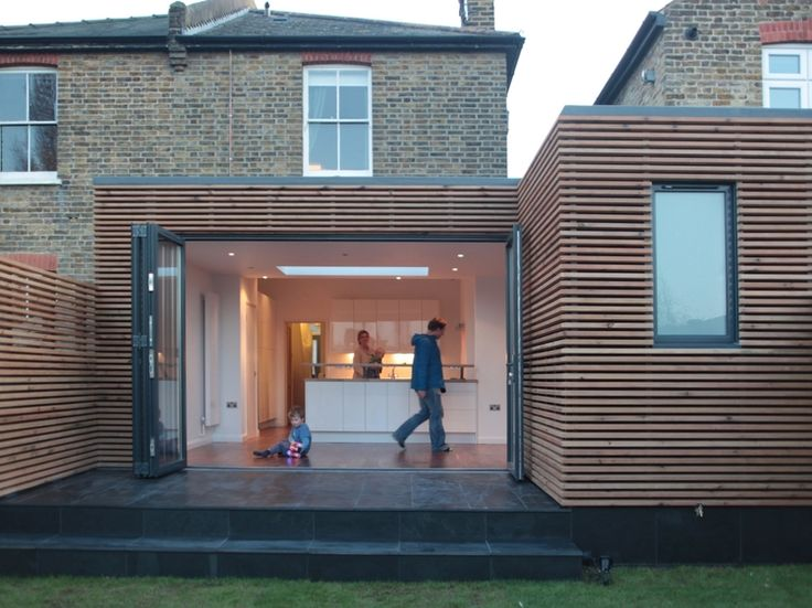I like how the wood cladding stands alone from the rest of the house - it announces that is an extension and does not try to be part of the original brick house.