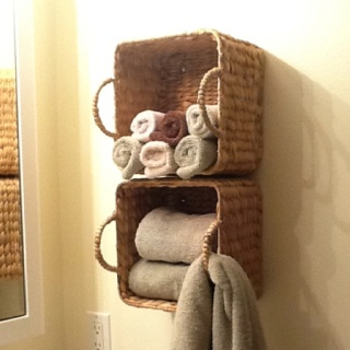 Baskets mounted on wall for bathroom towel storage. Awesome idea!