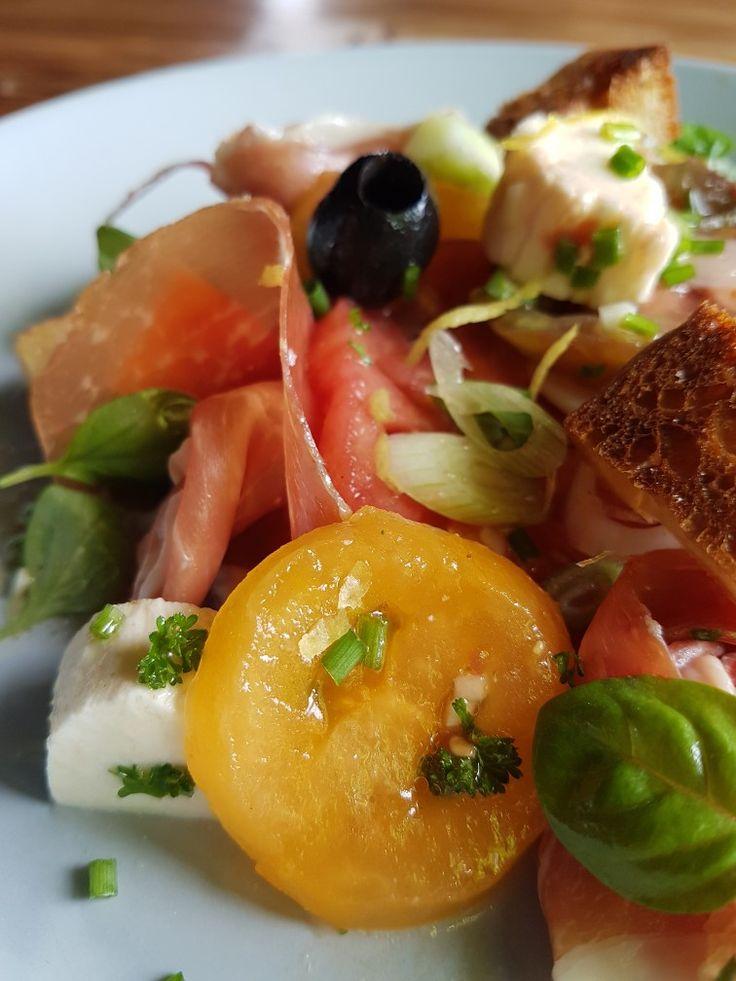 Slaatje van 5 verschillende kleurrijke tomaatjes, buffelmozzarella, gerookte ham, zwarte olijven en croûtons van ciabatta
