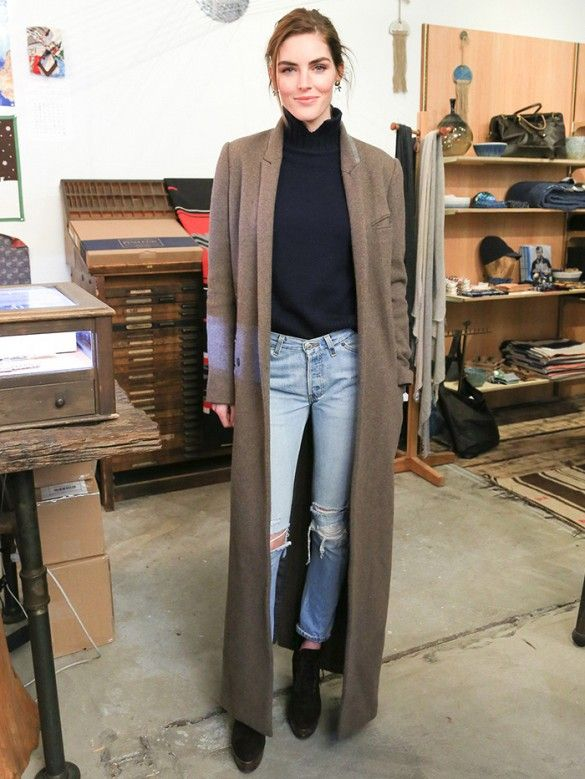 Hilary Rhoda wears her ripped jeans with a classy black turtleneck, long camel coat and black ankle boots.: