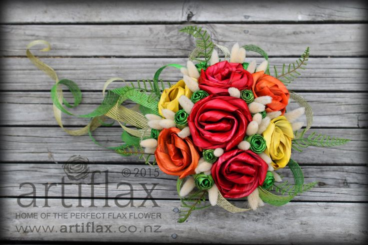 Cascading flax flower wedding bouquet by Artiflax  Vibrant red, orange and yellow flax flowers finished off with fresh green flax roses and beautiful bunny tails and hapene flax ribbon