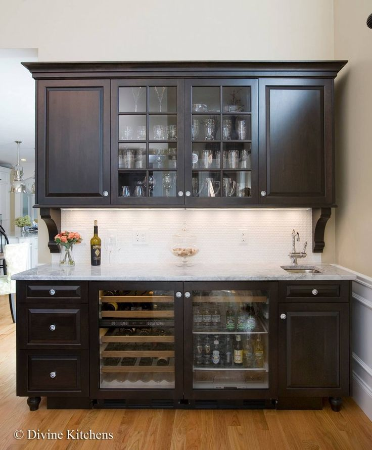 Wet bar with dark, raised-panel cabinetry, crown molding, corbels, wine & beverage fridge, and white stone countertop