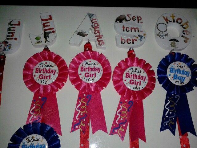 Verjaardagskalender voor in de klas. Letters en rozetten bij Xenos gekocht en met Mod Podge de namen van de maanden op de letters gezet. De rozetten hangen aan linten. natuurlijk mogen de kinderen hun rozet op als ze jarig zijn.