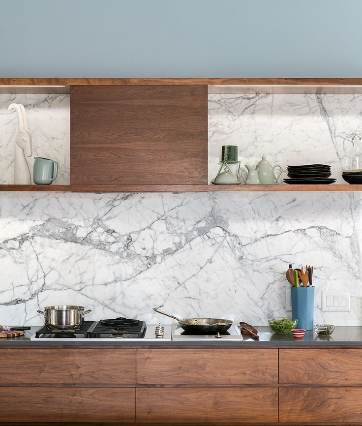 The walnut cabinetry was designed by Wilding; shelves have high-output LED tape routed into a continuous reveal for accent lighting.